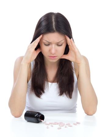 Vrouw met hoofdpijn blik op pillen geneeskunde tabletten op tafel tegen een witte achtergrond