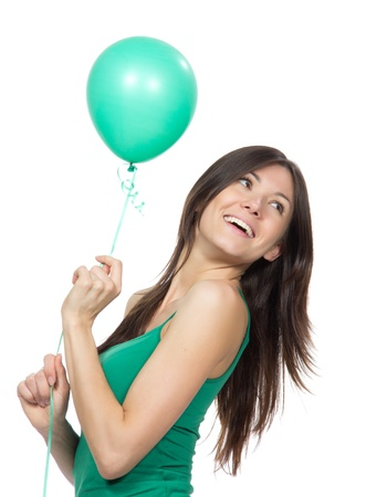 Young happy girl with green balloon as a present for birthday party smiling on a white background