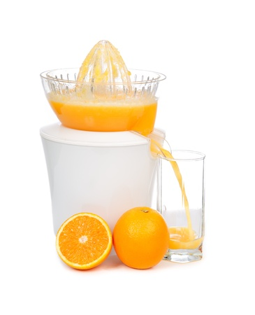 Preparing fresh orange juice squeezed with electric juicer on a white background photo