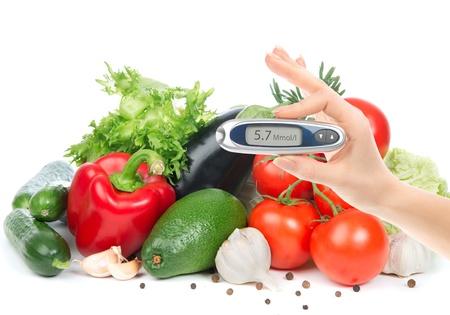 Diabetes begrip glucometer voor glucose niveau bloedtest in de hand en gezond biologisch voedsel op een witte achtergrond