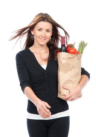 Young woman hold shopping paper bag full of vegetarian groceries, red pepper, salad, bottle of dry wine, asparagus, fresh organic tomatoes isolated on white background.