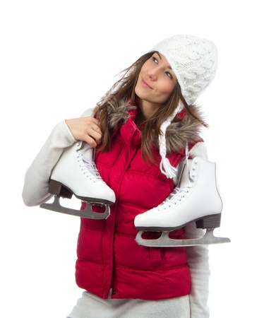 Young woman holding ice skates for winter ice skating sport activity in white hat smiling isolated on a white background photo