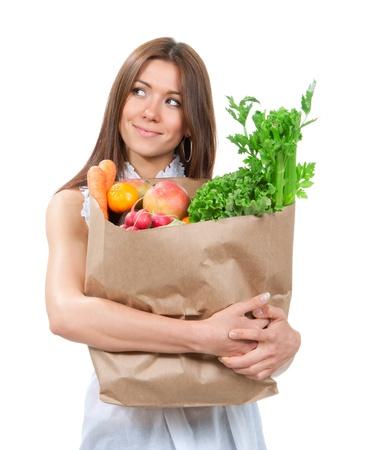 Happy jonge vrouw met een document het winkelen zak vol met boodschappen, mango, salade, asperges, radijs, avocado, citroen, wortelen op witte achtergrond