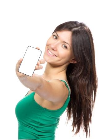 Jonge vrouw tonen weergave van de mobiele mobiele telefoon met wit scherm en lachend op een witte achtergrond. Focus op de hand met mobiele telefoon