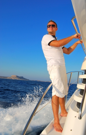 adult cruise: Young Sailor relaxing happily on the vacation sailboat yacht standing on a deck having a rest on summer boat over blue ocean wave splashes background Stock Photo