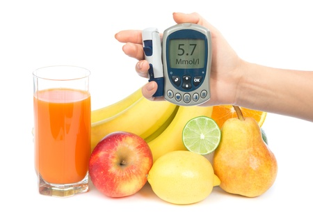 Diabetes concept glucose meter in hand and healthy organic food,  lemon, pear, apple, fresh orange, bananas and carrot juice on a white background photo