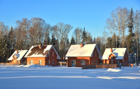 Winter countryside snowy houses cottage in morning  in a beautiful snow forest on  a blue sky background photo
