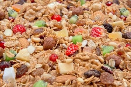 Muesli cereals background with almond, pine nuts, walnut,  raisins, oat and wheat flakes, sultanas, fresh fruits kiwi, strawberry pieces, banana, pomegranate seeds  photo
