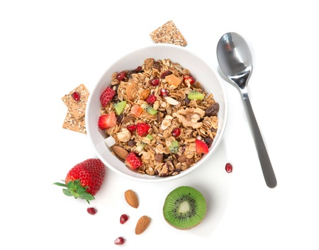 Muesli cereals bowl and spoon with almond, pine nuts, walnut,  raisins, oat and wheat flakes, sultanas, fresh fruits kiwi, strawberry pieces, banana, pomegranate seeds Stock Photo