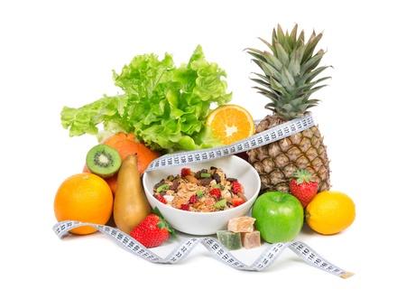 Dieet gewichtsverlies ontbijtconcept met meetlint organische groene appel, granen kom, jus d'orange, ananas, muesli granen kom, peer, kiwi, citroen, Rahat vreugde, aardbeien op een witte achtergrond Stockfoto