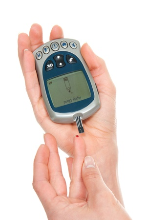 poking: Diabetes patient measuring glucose level blood test using ultra mini glucometer and small drop of blood from finger and test strips isolated on a white background Stock Photo