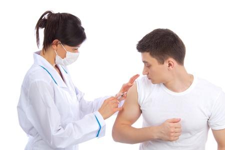 Arts vrouw in masker geven griepvaccinatie of insuline-injectie geschoten om een patiënt op een witte achtergrond
