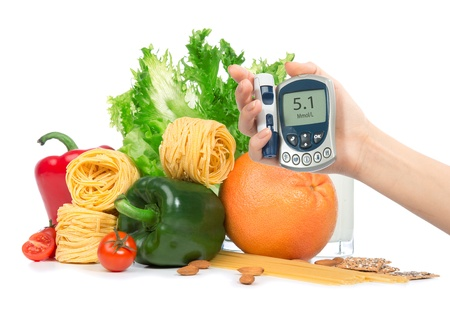 Diabetes concept glucose meter in hand and healthy organic green and red pepper, tomatoes, almonds, fresh salad, spaghetti, grapefruit, glass of milk on a white background photo