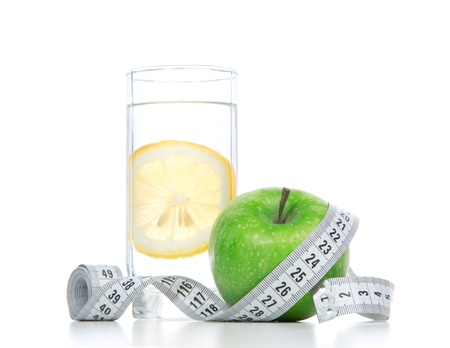Diet diabetes weight loss concept with tape measure organic green apple and glass of drinking water with lemon on a white background. Focus on water photo