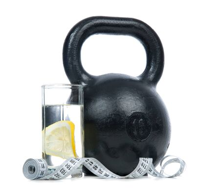 fitness equipment: Big black fitness weight with tape measure and glass of drinking water with lemon isolated on a white background. Healthy lifestyle weight loss concept