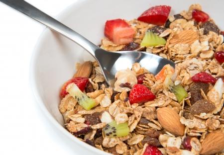 comiendo cereal: Muesli cereales taz? una cuchara de almendras, pi?s, nueces, pasas, avena y copos de trigo, pasas, kiwi fruta fresca, trozos de fresa, pl?no, semillas de granada