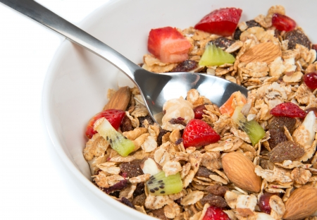 breakfast cereal: Muesli cereals bowl and spoon with almond, pine nuts, walnut, raisins, oat and wheat flakes, sultanas, fresh fruits kiwi, strawberry pieces, banana, pomegranate seeds