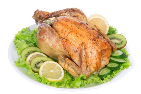 Garnished roasted thanksgiving chicken on a plate decorated with salad isolated on a white background photo