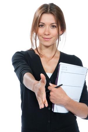 若いブルネットのビジネスの女性を与えるハンドシェイクとカジュアルな布の白い背景で隔離の笑みを浮かべて