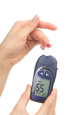 Diabetes patient measuring glucose level blood test using glucometer and small drop of blood from finger and test strips isolated on a white background