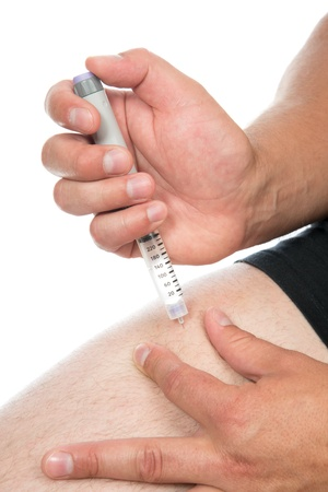 Diabetes patient make insulin injection shot by syringe subcutaneous leg vaccination isolated on a white background photo
