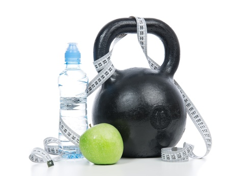 Big black fitness weight dumbbell with tape measure, drinking water and apple isolated on a white background. Healthy lifestyle weight loss concept