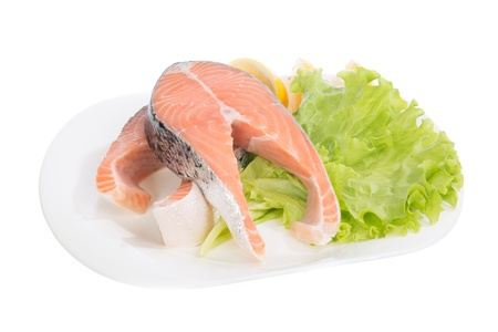 Raw salmon steaks red fish on a plate decorated with fresh lemon and salad isolated ona white background photo