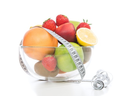 Diet weight loss breakfast concept with tape measure fruits, organic green apple, orange lemon, peach, grapefruit strawberries on a white background photo