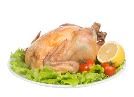 Garnished roasted thanksgiving chicken on a plate decorated with salad, lemon, tomatoes cherry isolated on a white background