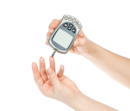 blood sugar: Diabetes patient measuring glucose level blood test using mini glucometer and small drop of blood from finger and test strips isolated on a white background Stock Photo