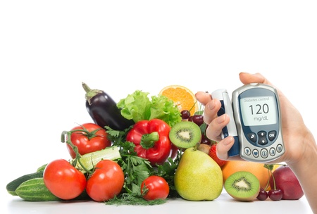 Diabetes begrip glucosemeter in de hand en gezonde biologische voeding groenten en fruit biologische groene appel, aubergine, sinaasappel, tomaten, komkommers, peterselie, kiwi, grapefruit, salade, perzik, kersen op een witte achtergrond Stockfoto