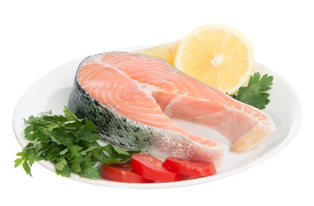 Raw fresh salmon steaks red fish on a plate decorated with fresh lemon, tomatoes and salad isolated ona white background photo