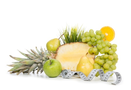 Diet weight loss breakfast concept with tape measure and fruits organic green apple, pears, pineapple, orange slice, lemon, grapes on a white background photo