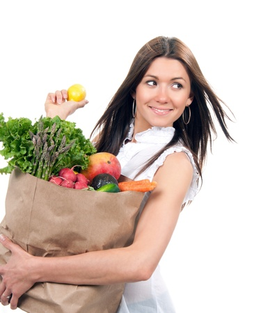 Young woman holding shopping bag with groceries vegetables and fruits isolated on white background. Healthy eating concept