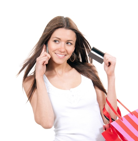 Happy young woman with shopping bags and credit card in hand talking on phone isolated on a white background photo