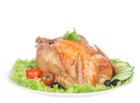 Garnished roasted thanksgiving chicken on a plate decorated with salad, olives, tomatoes, cucumbers isolated on a white background