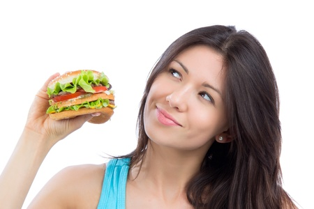 Young woman with tasty fast food unhealthy burger in hand to eat isolated on a white background photo