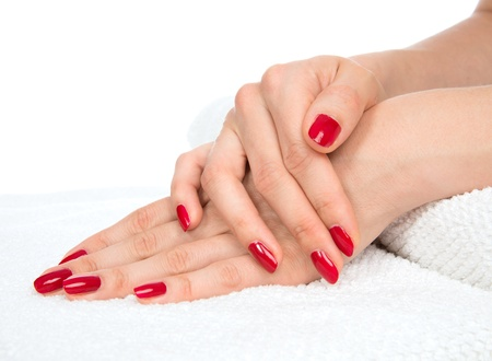 salon background: Woman hands with manicured red nails isolated on a white background. Skin and nail care concept