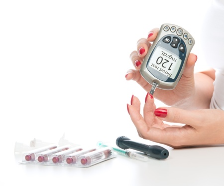Diabetes patient measuring glucose level blood test using mini glucometer and small drop of blood from finger and test strips isolated on a white background Banque d'images