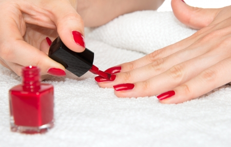 Woman hands doing manicure red nails on a white background. Skin and nail care salon concept