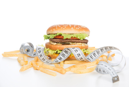 Burger cheeseburger meal with french fries chips tape measure on white background. Healthy weight loss diet concept. photo