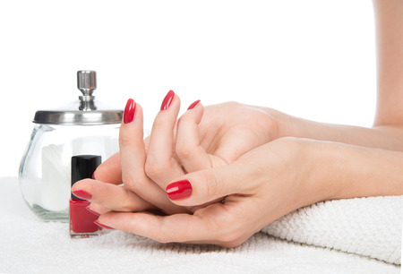bodycare: Woman hands manicure red nails on a white background. Skin and nail care salon concept