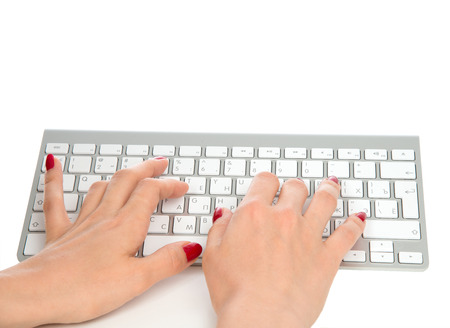 Hands typing on the remote wireless computer keyboard in an office at a workplace isolated on a white background photo