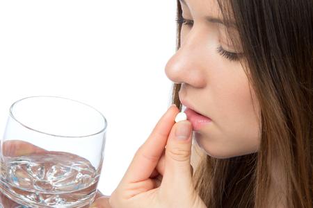 personas tomando agua: Mujer con la mano dolor de cabeza tomar la p�ldora tablet medicina y vaso de agua aislado en un fondo blanco