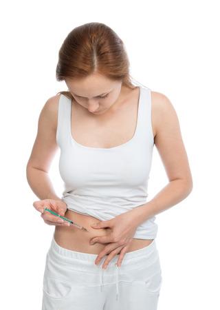 Diabetes vrouw patiënt maakt een buik subcutane insuline spuit injectie inenting geschoten op een witte achtergrond