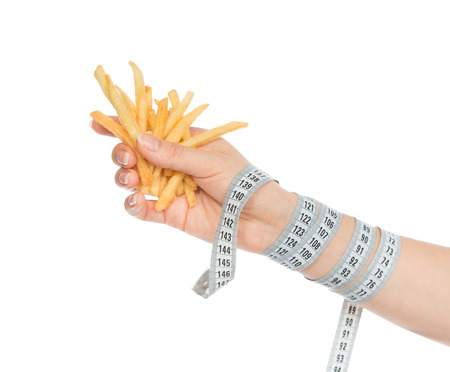 French fries chips in hand with tape measure on white background. Healthy weight loss diet concept. photo