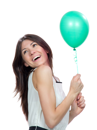 Young happy girl with green balloon as a present for birthday party smiling and looking at the corner on a white background photo
