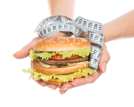 Burger cheeseburger in hands with measure tape isolated on white background. Healthy weight loss diet concept. photo