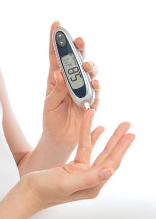 diabetes syringe: Diabetes patient measuring glucose level blood test with glucometer from finger on a white background Stock Photo