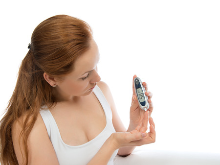 Diabetes patient woman measuring glucose level blood test with glucometer on a white background Stok Fotoğraf
